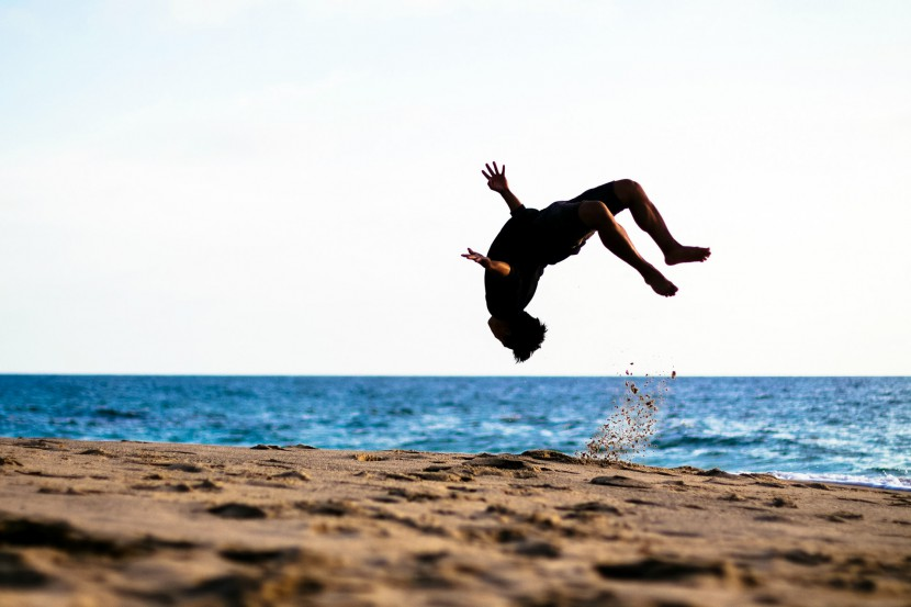 Man doing a backflip on the beach