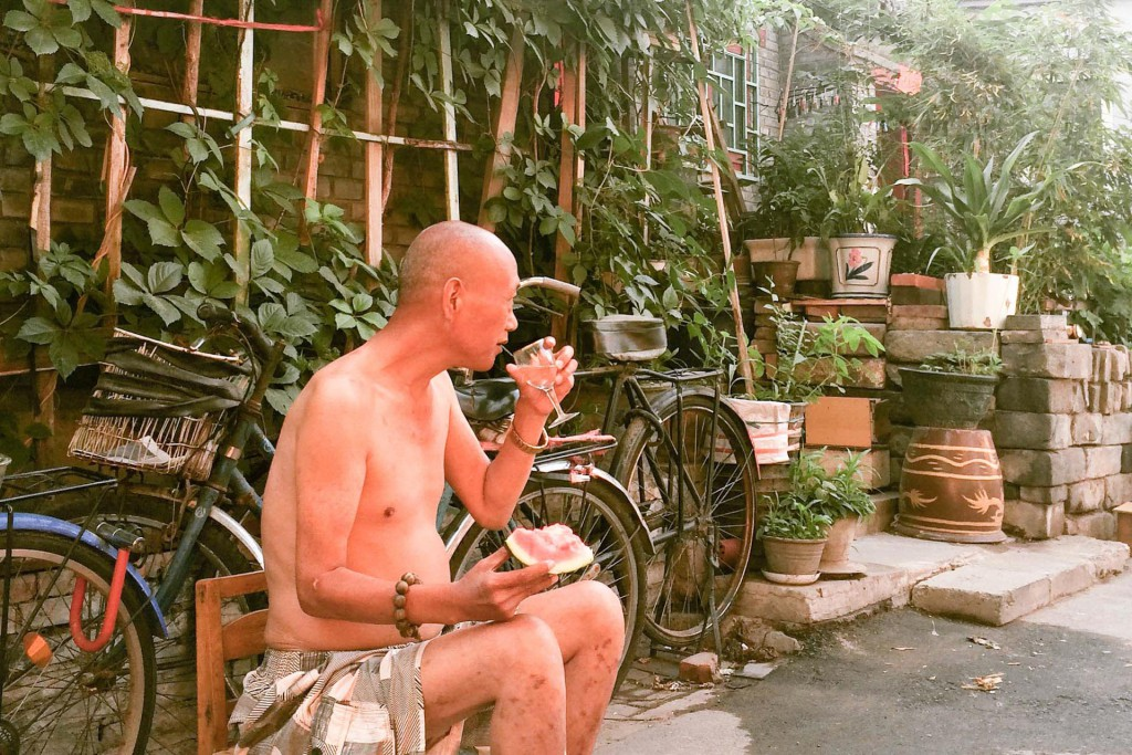 An old man drinking in a hutong