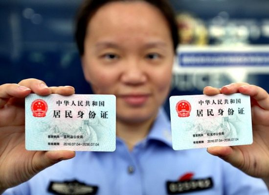a-police-officer-in-shanghai-shows-two-identification-cards-issued-to-nonlocal-residents-in-the-city